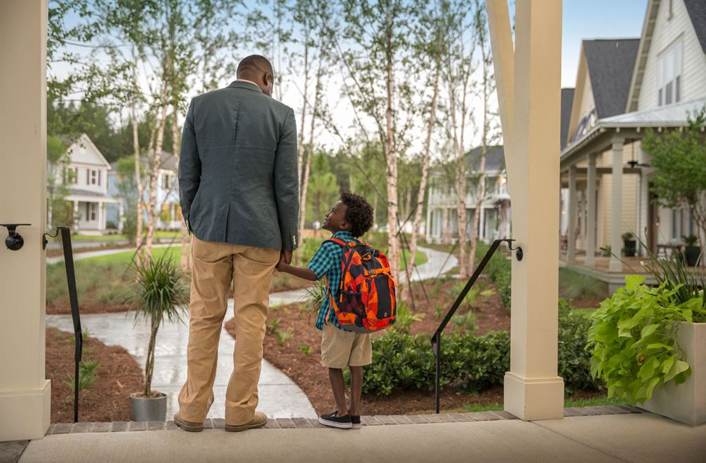 A father and son hold hands on a porch about to go to school