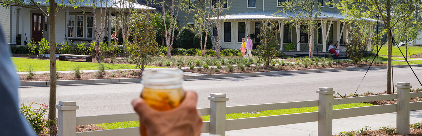 Streetscape of Nexton, with person holding cup of iced tea along sidewalk.