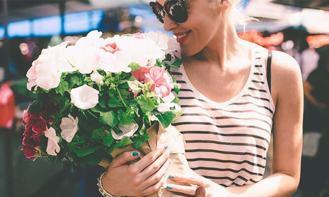 A woman holds a bouquet of flowers while shopping in Summerville SC