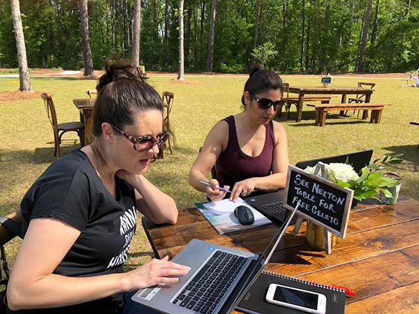 Women working on computers at picnic table in park at Nexton.