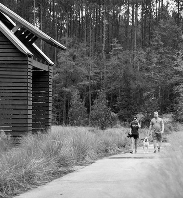 Black and white image of a couple walking along a trail in Nexton.