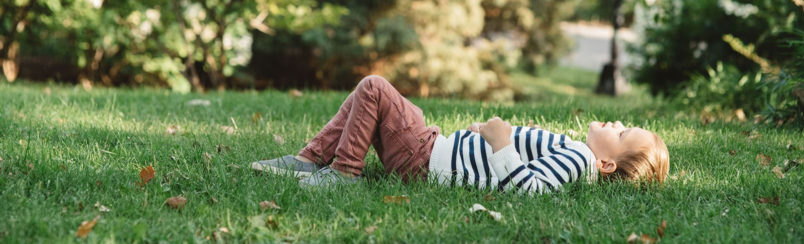 Boy laying in the grass in one of Nexton's many parks.